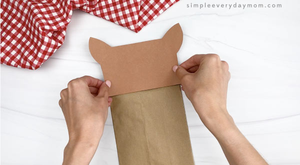 hand gluing head to paper bag horse craft