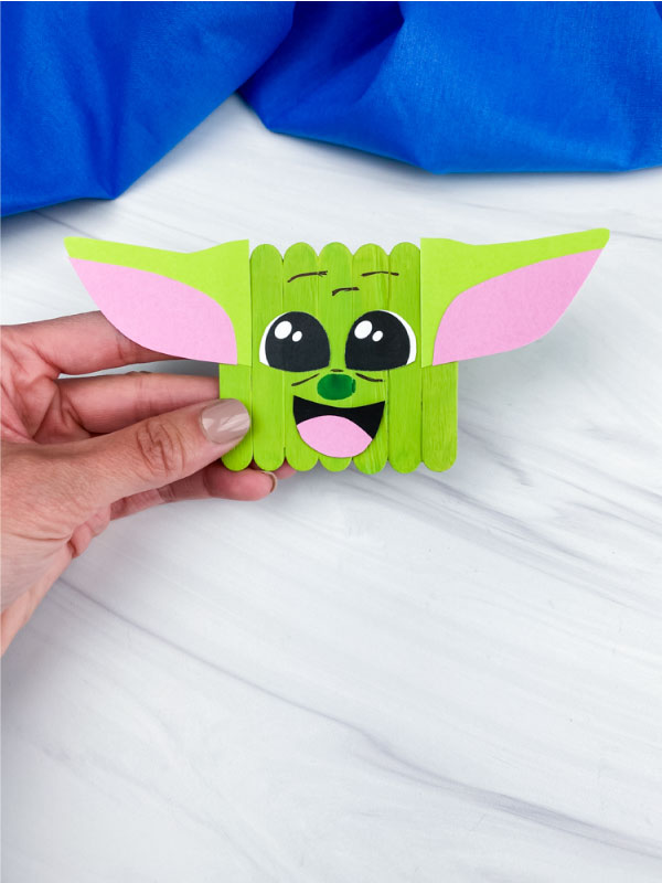 hand holding popsicle stick baby yoda craft