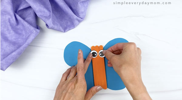 hand gluing eyes to popsicle stick butterfly craft