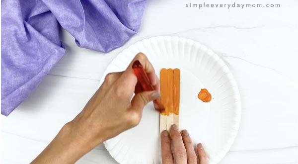 hand painting popsicle stick orange