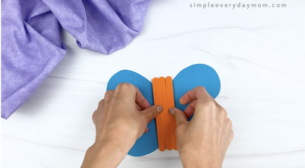 hand gluing popsicle stick body to popsicle stick butterfly craft