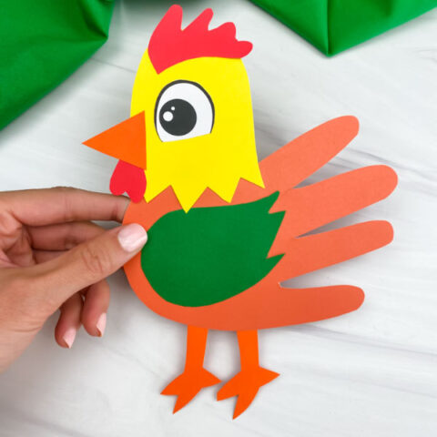 hand holding handprint rooster craft