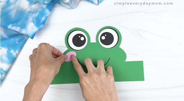 hand gluing cheek to frog headband craft