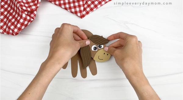 hand gluing head to handprint body