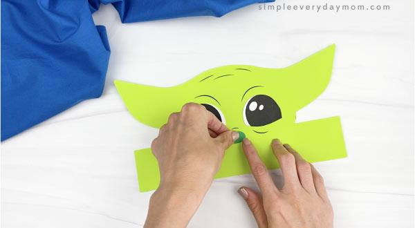 hands gluing nose to Baby Yoda headband craft