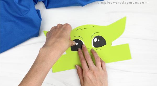 hands gluing eyes to Baby Yoda headband craft