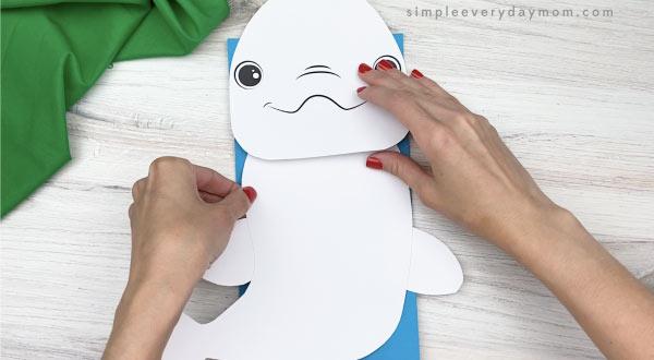 hand gluing body to paper bag beluga craft