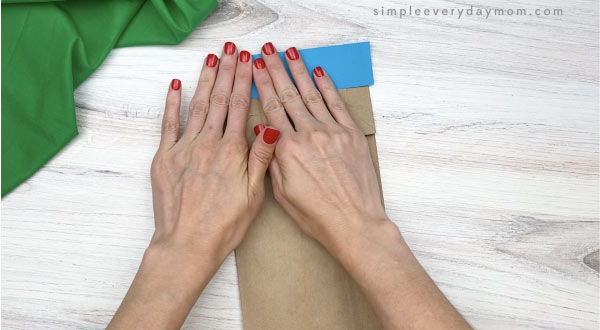 hand gluing blue rectangle to paper bag beluga craft