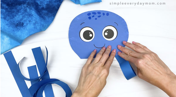 hand gluing tentacles onto paper plate octopus craft
