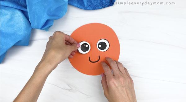 hand gluing eye to handprint octopus