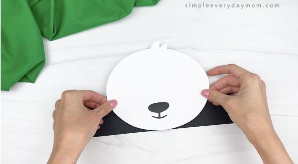 hand gluing head to panda headband craft base