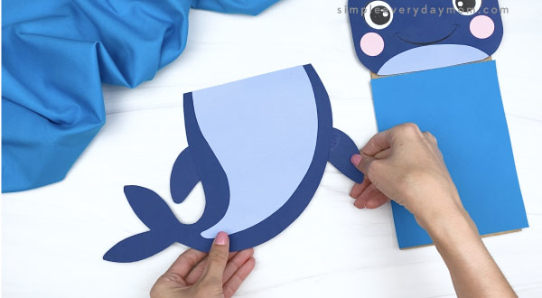 hands gluing fin to paper bag whale craft