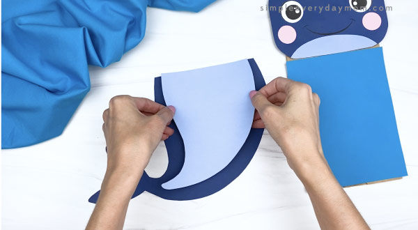 hands gluing belly to paper bag whale craft