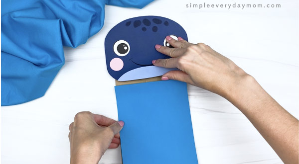 hands gluing blue rectangle to paper bag whale craft