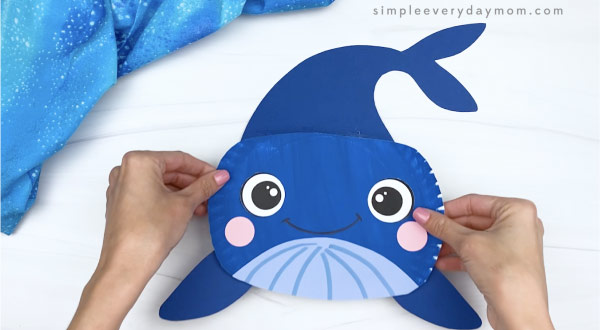 hand gluing tail onto paper plate whale craft