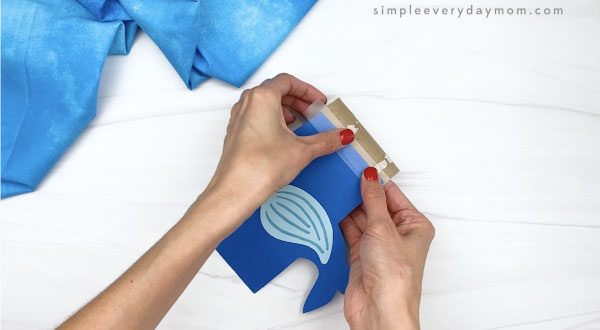 hand taping whale body to toilet paper roll