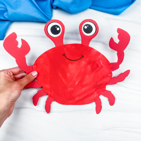hand holding paper plate crab craft