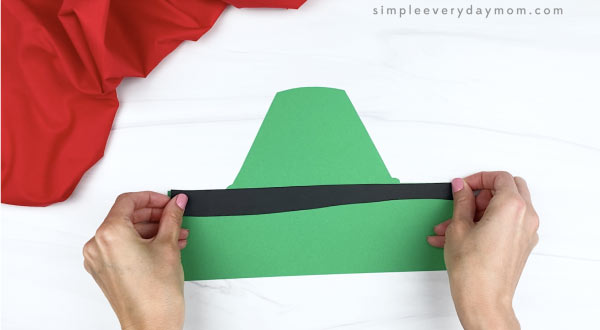 hands gluing black line decoration on crayon headband craft