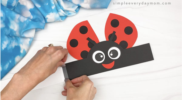 hand taping extender to ladybug headband craft