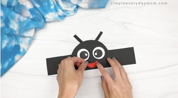 hand gluing mouth to ladybug headband craft