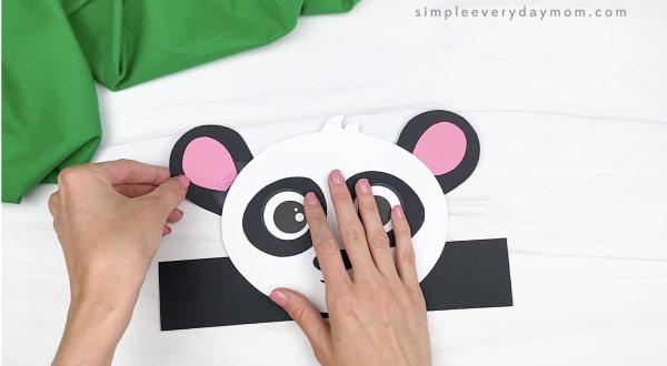 hand gluing ears to panda headband craft