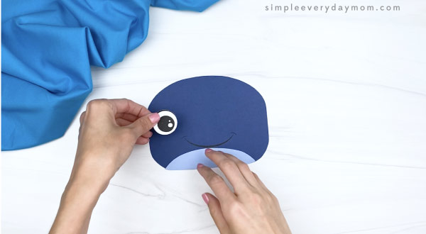 hands gluing eyes to paper bag whale craft