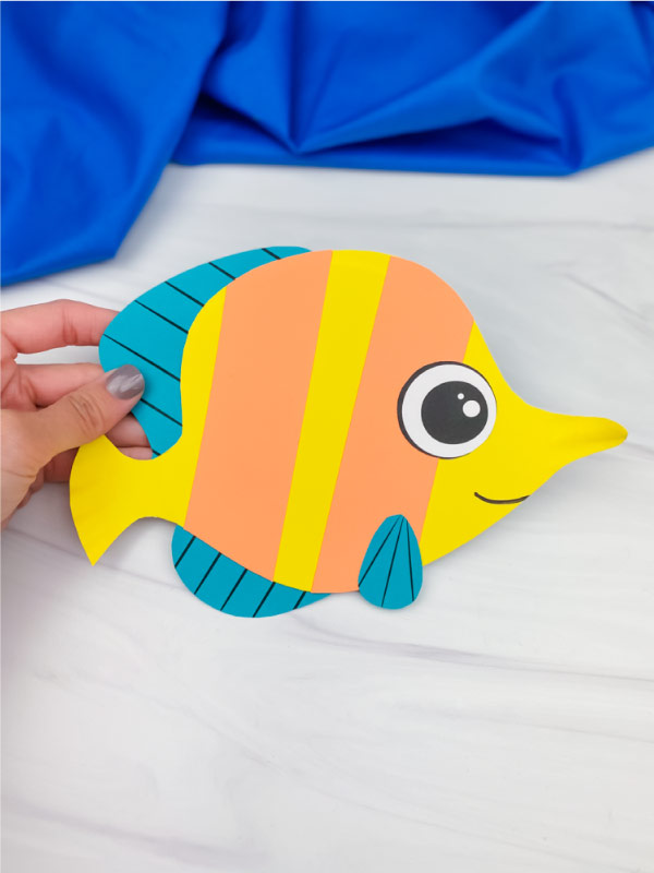 hand holding paper plate fish craft