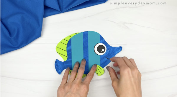hand gluing side fin to paper plate fish