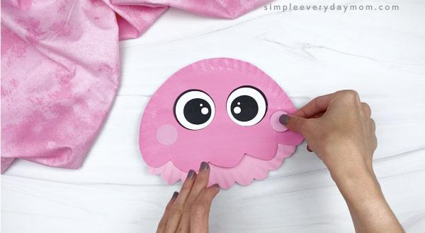 hand gluing cheeks to paper plate jellyfish
