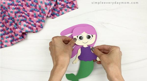 hand gluing hair to handprint mermaid craft