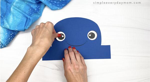 hand gluing eyes to humpback whale headband craft