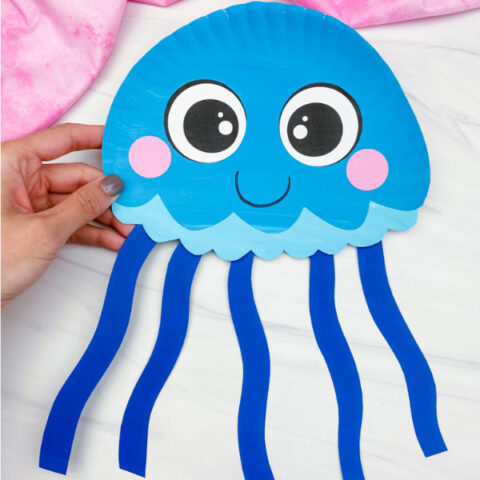 hand holding blue paper plate jellyfish