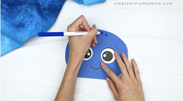 hand drawing spots on top of paper plate octopus head