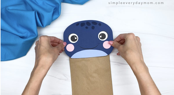 hands gluing head to paper bag whale craft