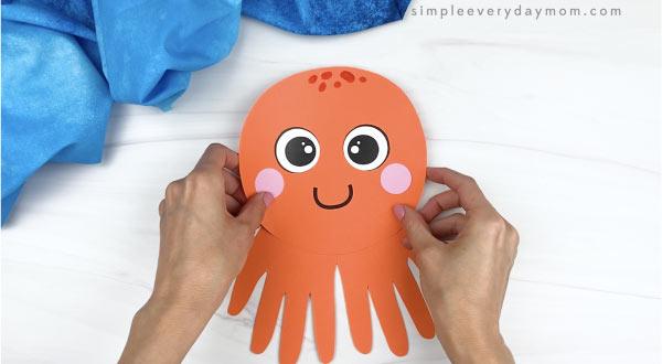 hand gluing head to handprint octopus