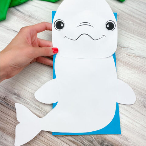 hand holding paper bag beluga whale craft