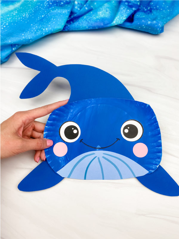 hands holding paper plate whale craft
