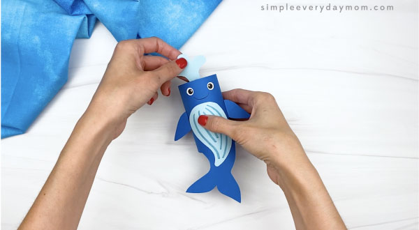 hand gluing water to top of toilet paper roll humpback whale craft