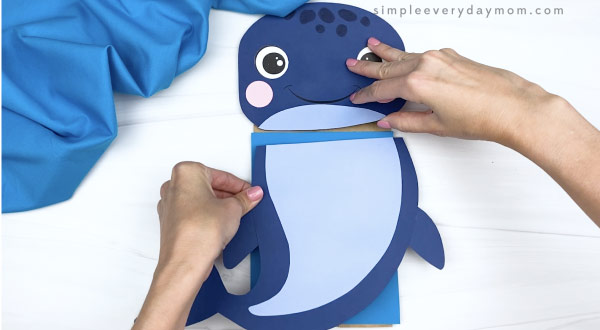 hands gluing body to paper bag whale craft