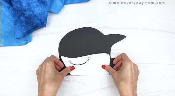 hand gluing mouth to killer whale headband craft