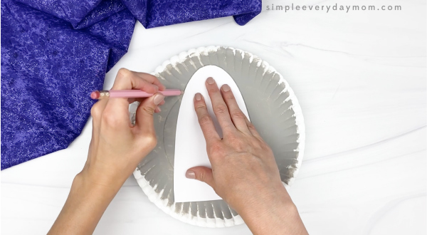 hand tracing rocket template onto paper plate