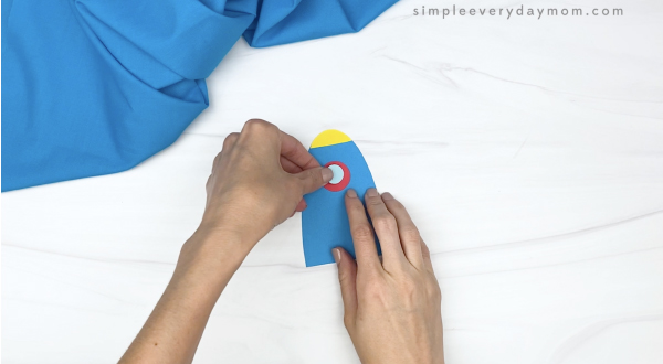hand gluing window onto toilet paper roll craft
