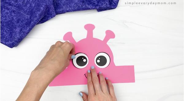 hand gluing eye to alien headband craft