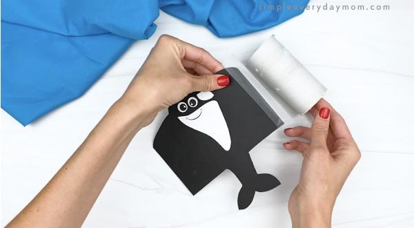 hand taping killer whale paper onto cardboard tube