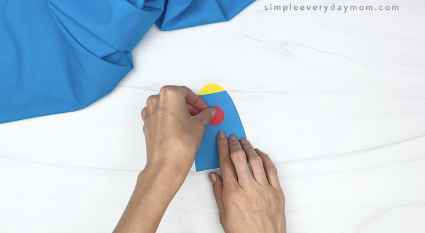 hand gluing window frame onto toilet paper roll craft