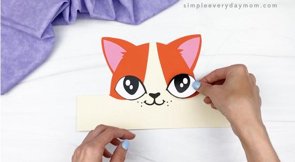 hand gluing eye to cat headband craft