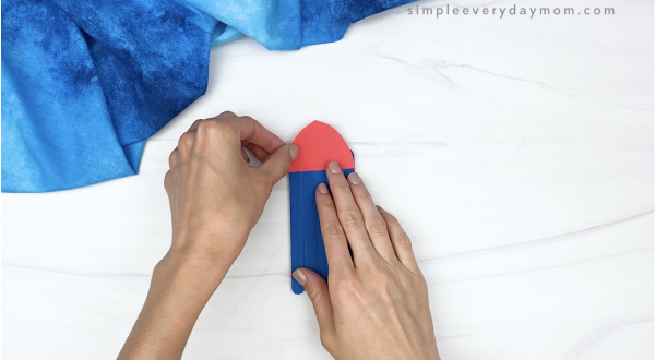 hand gluing tip to popsicle stick rocket craft