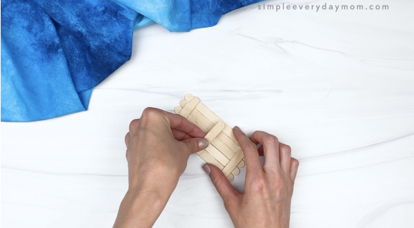 hand gluing popsicle stick together