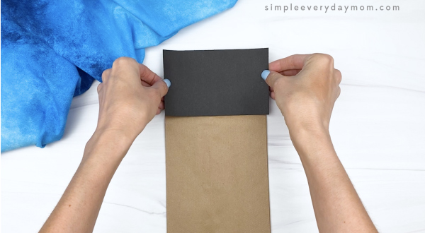 hand gluing black paper to brown paper bag