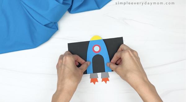 hand gluing rocket to black background